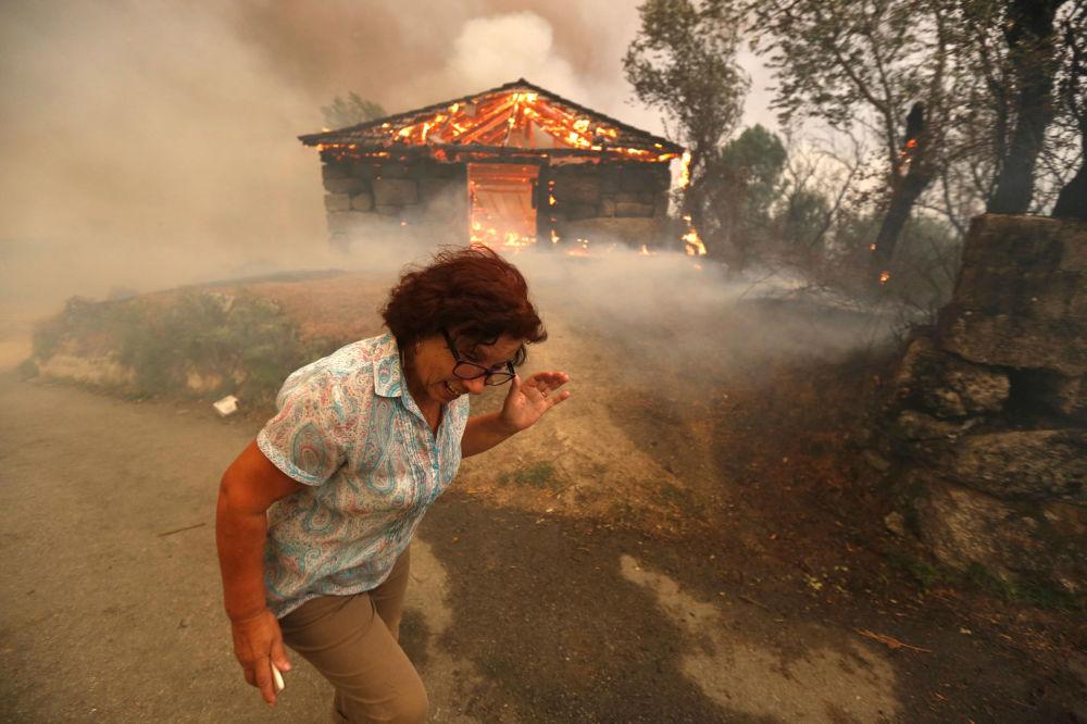 امرأة تهرب من الحريق في قرية أوتيرو، خلال اندلاع الحرائق الهائلة التي تشهدها البرتغال في الآونة الأخيرة، 13 أغسطس/ آب 2016