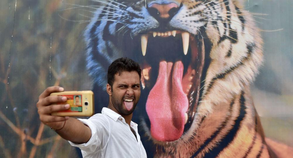 رجل هندي يأخذ صورة سيلفي له على خلفية جدارية كبيرة لحيوان النمر ، خلال مهرجان بهرات باراف في نيودلهي، الهند 18 أغسطس/ آب 2016