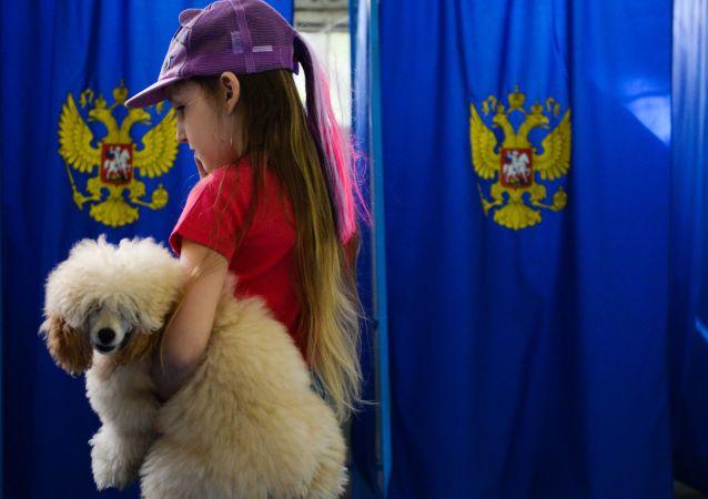 فتاة مع كلب خلال التصويت في الانتخابات البرلمانية الروسية فى مركز اقتراع في نوفوسيبيرسك