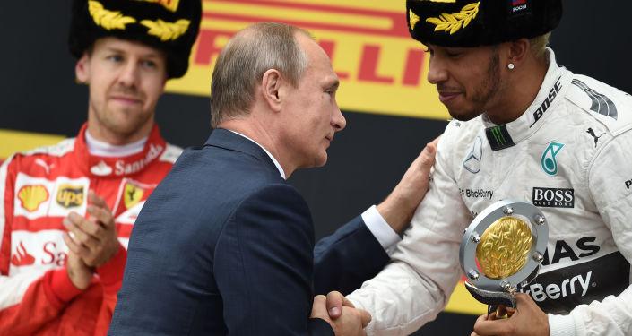 الرئيس الروسي فلاديمير بوتين يسلّم كأس بطولة غراند بريس (فورمولا-1) للمتسابق لويس هاملتون في مدينة سوتشي.