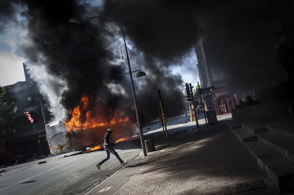 أحد المتظاهرين يجري في الشارع بعد انفجار باص في جوهانسبرغ، جنوب أفريقيا 10 أكتوبر/ تشرين الأول 2016
