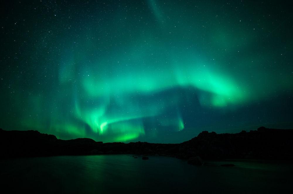 لغز الجمال الساحر لشمال روسيا - الشفق القطبي الشمالي فوق قرية تيريبيركا بمقاطعة مورمانسك.