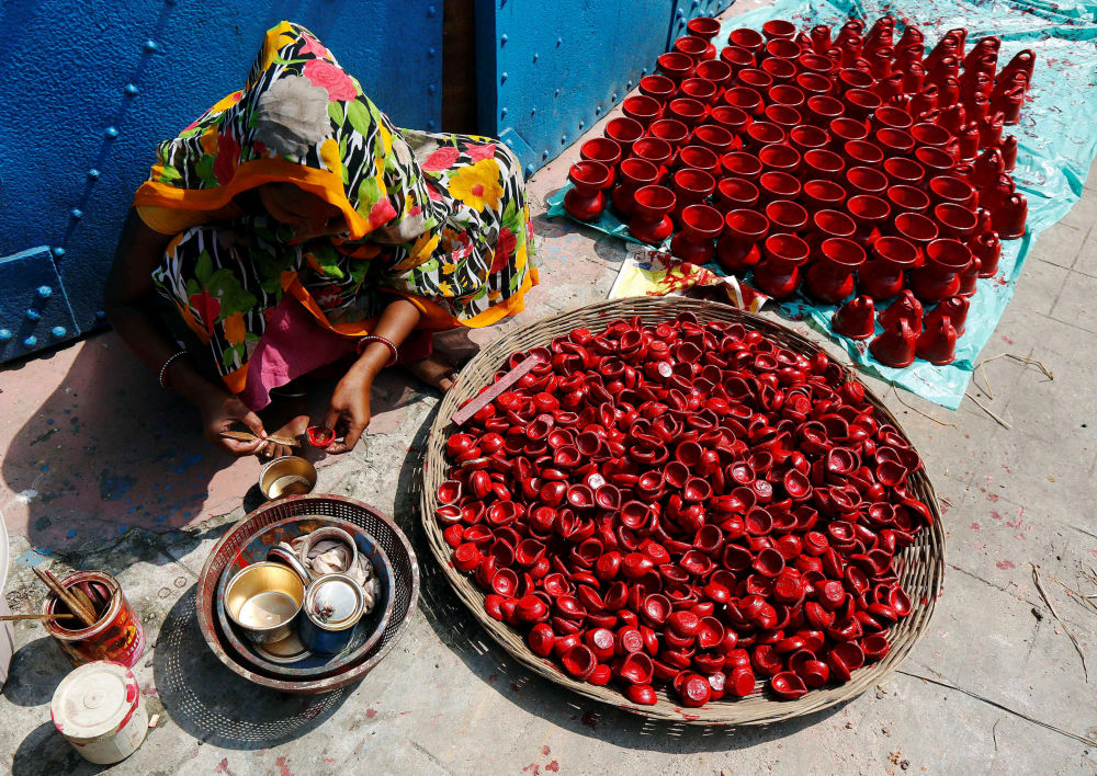 امرأة ترسم المصابيح الترابية في كلكتا، الهند