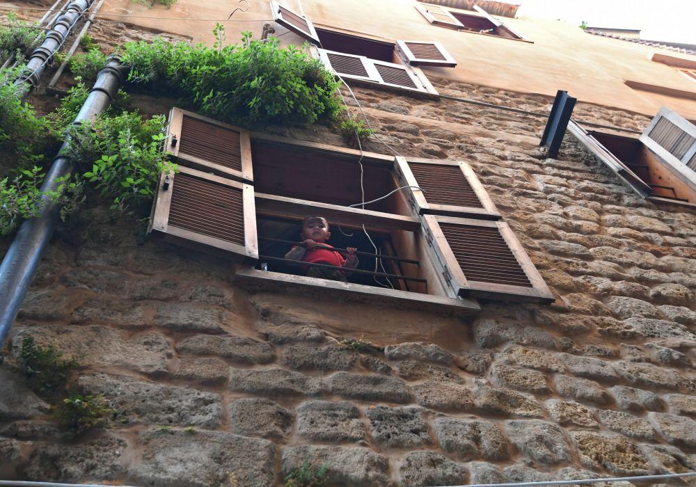 طفل صغير يطل من نافذة بيته في ميدنة صيدا
