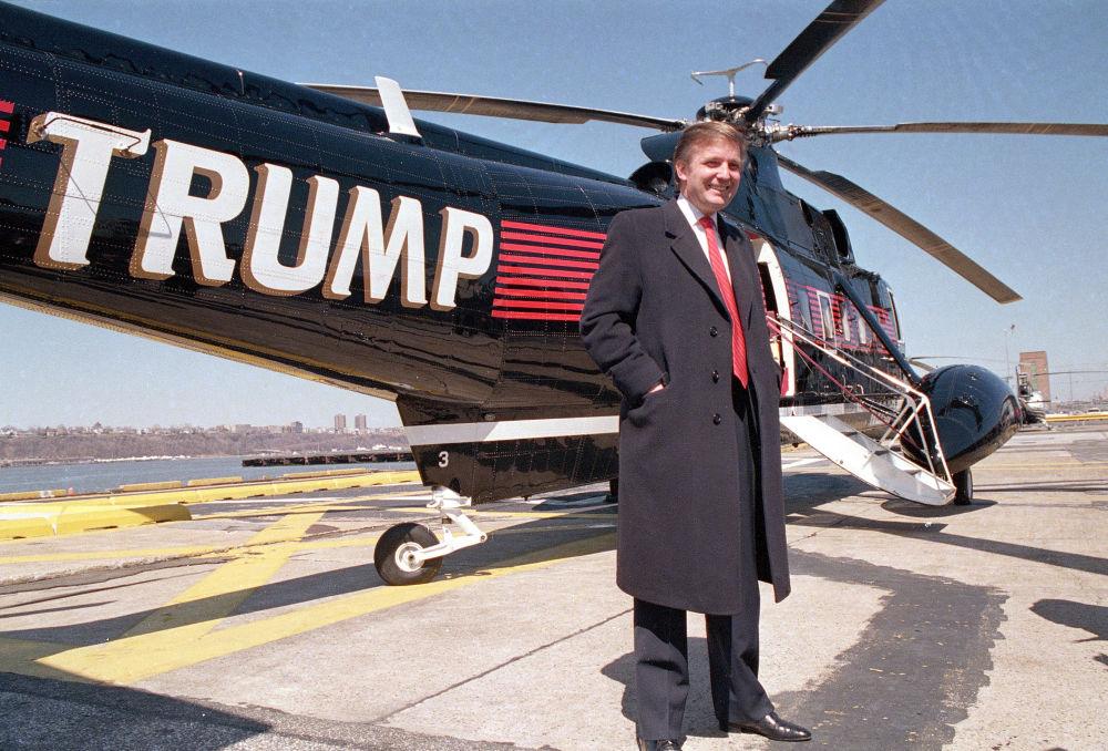 المرشح للانتخابات الرئاسية من الحزب الجمهوري دونالد ترامب يقف أمام مروحيته الخاصة بميناء نيويورك الجوي، 22 مارس/ آذار 1988