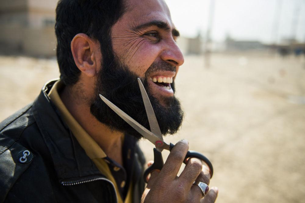 رجل عراقي يقوم بقص شعر ذقنه بواسطة مقص، وذلك لدى وصوله المناطق التي حررتها القوات العراقية بحي الانتصار بالموصل، 7 نوفمبر/ تشرين الثاني 2016