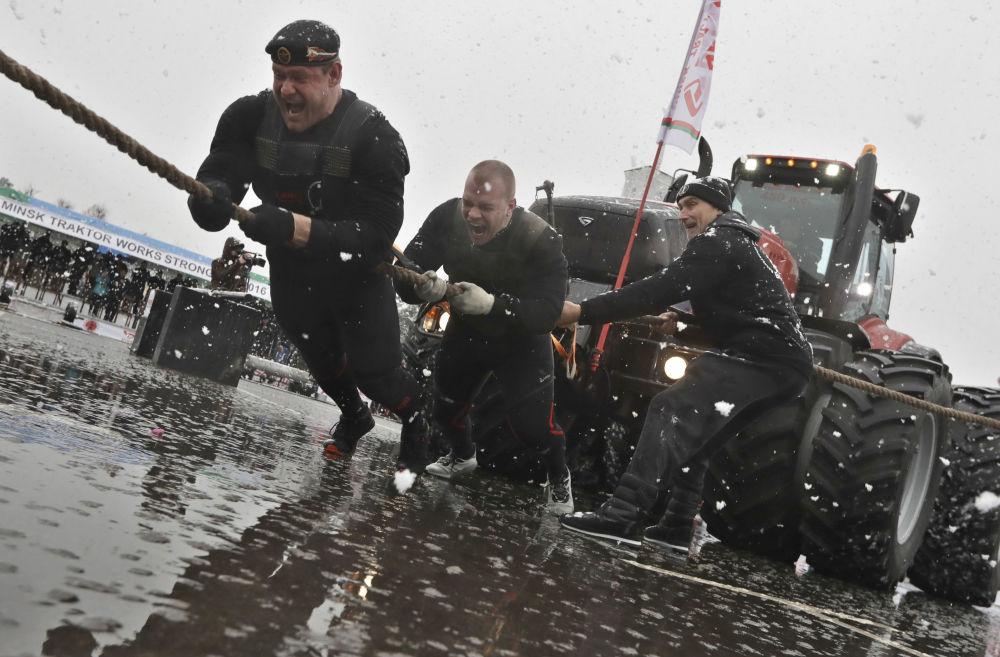 الرياضي البيلاروسي دميتري بيلايتس والرياضي الروسي ميخائيل شيفلياكوف يجران مركبة جديدة بيلاروسي 4522 خلال فعالية عرض المركبة بالقرب من مصنع مينسك  للمركبات، بيلاروسيا 7 نوفمبر/ تشرين الثاني 2016