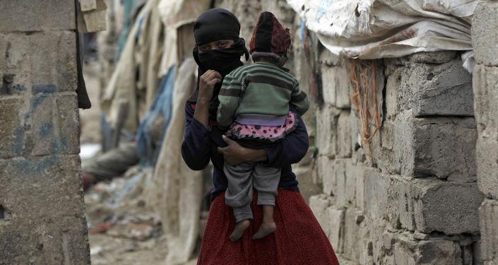 امرأة تحمل طفلها، من مجتمع الخدام، تسير وسط أحد الأحياء الفقيرة في العاصمة صنعاء، اليمن 9 نوفمبر/ تشرين الثاني 2016