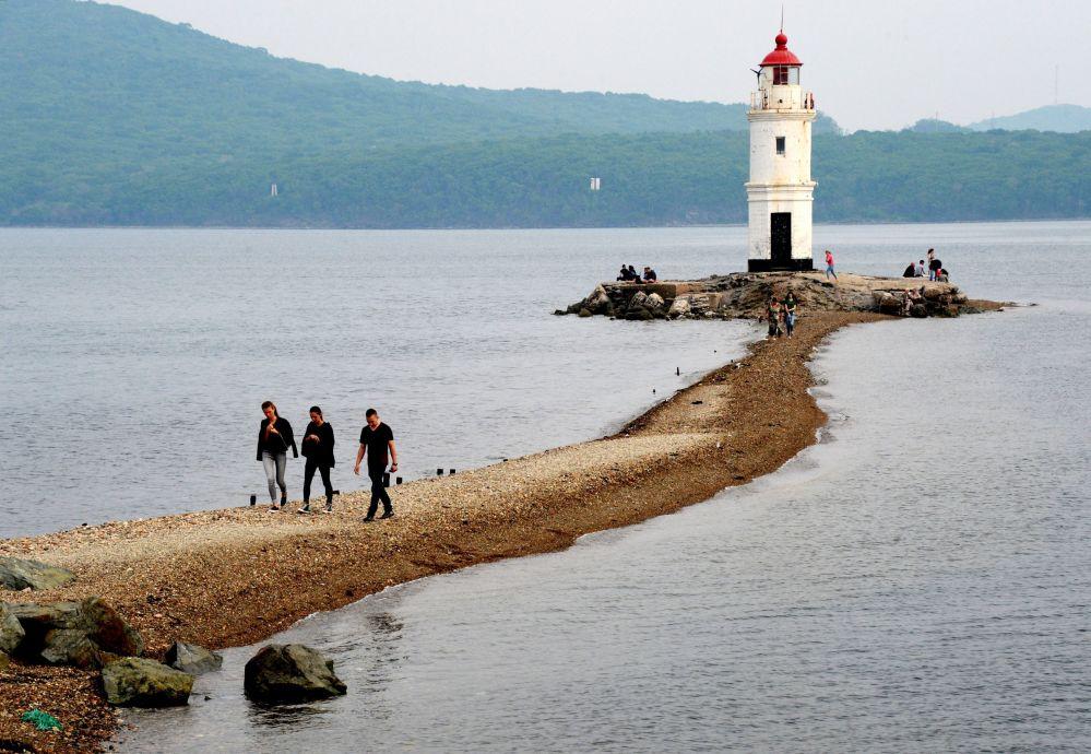 زوار يصطافون على اللسان الصخري لمنارة توكاريف - الذي يرمز لـ نهاية الأرض، حيث يبدأ المحيط الهادئ.