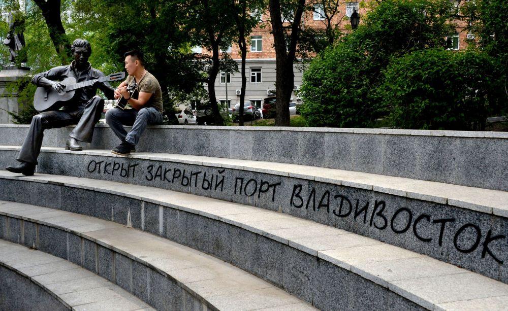 رجل يلعب على الغيتار بجوار تمثال الفنان والشاعر فلاديمير فيسوتسكي في ساحة تياترالني في مدينة فلاديفوستوك
