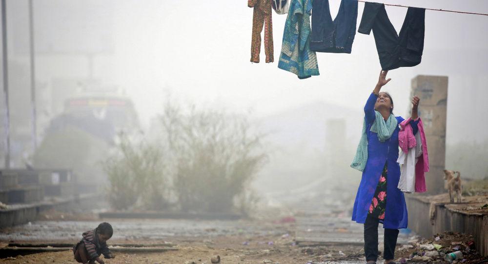امرأة تجمع الغسيل وضباب كثيف يغطي مدينة دلهي، الهند 1 ديسمبر/ كانون الأول 2016