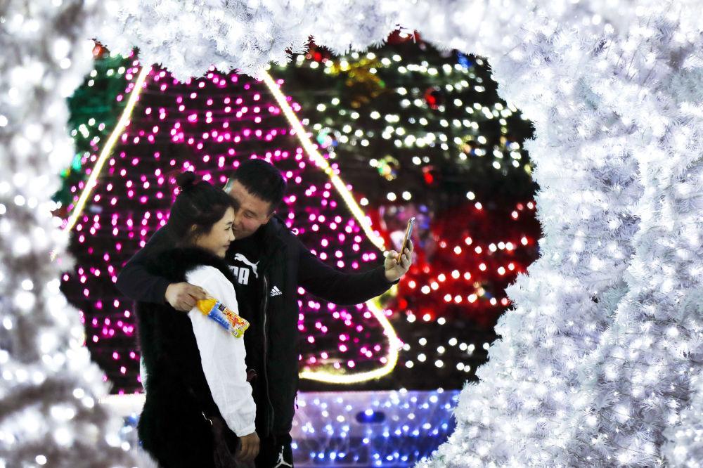 حبيبان، رجل وامرأة يلتقطان صورة سيلفي على خلفية أضواء أعياد رأس السنة في بكين، 1 ديسمبر/ كانون الأول 2016