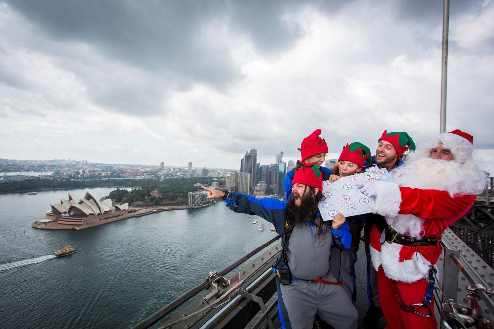 مجموعة من أشخاص يرتدون زس سانتا كلاوز يقفون أعلى جسر سيدني هاربر بريدج ويشيرون إلى المنازل التي سيرسلون الهدايا إليها، أستراليا، 7 ديسمبر/ كانون الأول 2016