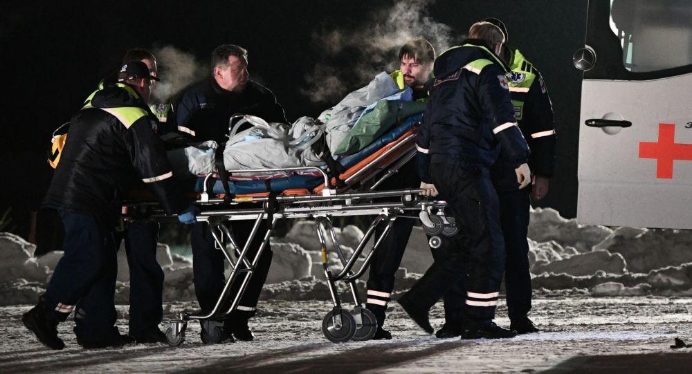 عناصر من الفريق الطبي التايع لوزارة الطوارئ الروسية يقومون بإخراج أطفال من طائرة _تابعة لوزارة الطوارئ) الذين تم إيصالهم إلى مستشفيات موسكو بعد تعرضهم لحادث سير في خانتي-مانتيسك