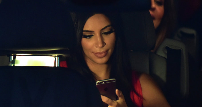 US reality TV star Kim Kardashian looks at her iPhone as she sits in a car after visiting the genocide memorial, which commemorates the 1915 mass killing of Armenians in the Ottoman Empire, in Yerevan on April 10, 2015
