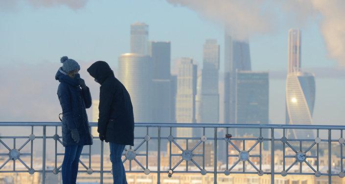 شخصان يقفان على خلفية ناطحات سحاب لـ موسكو سيتي، ودرجة الحرارة 27 درجة مئوية تحت الصفر.