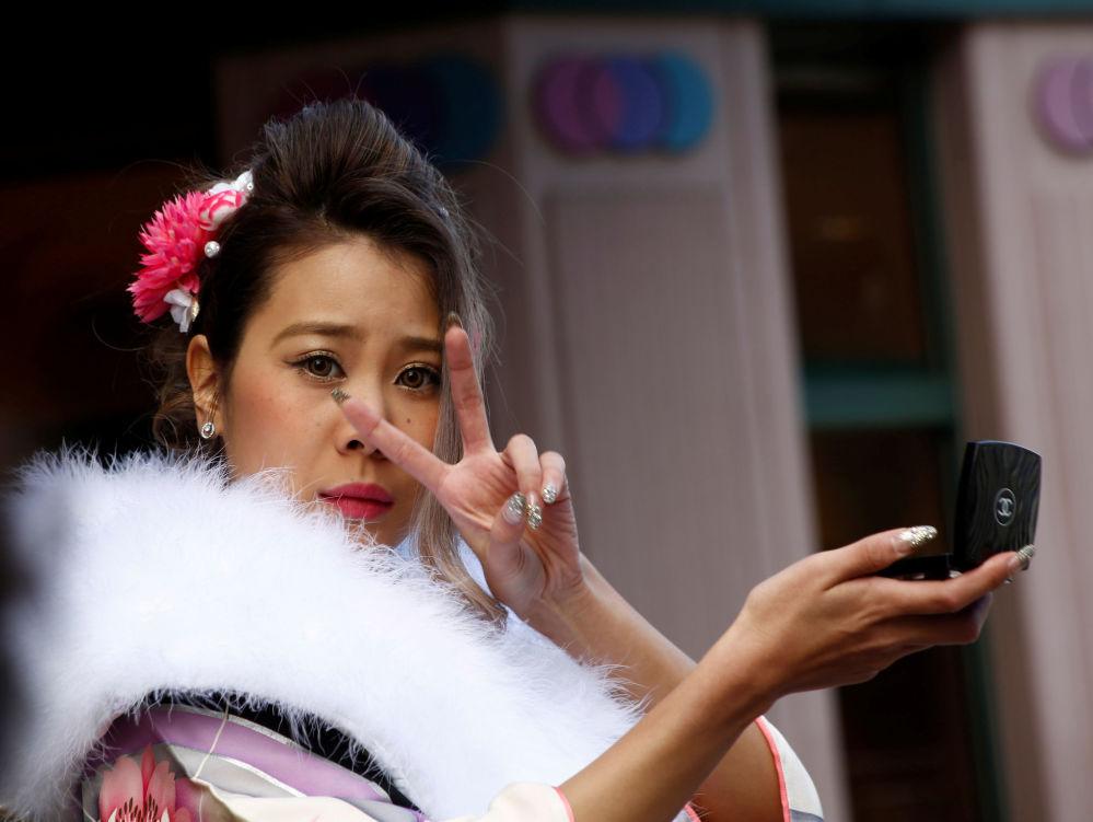 فتاة يابانية ترتدي الزي التقليدي الياباني كيمونو تمسك بمرأتها وتتحقق من المكياج، اليابان 9 يناير/ كانون الثاني 2017