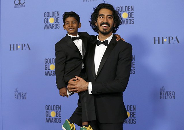 Actor Dev Patel holds actor Sunny Pawar, who portrays the same character as Patel in the movie Lion