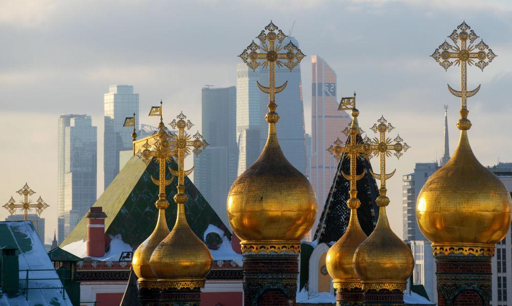 منظر لقبب كنيسة في موسكو يظهر خلفها حي موسكو سيتي الحديث