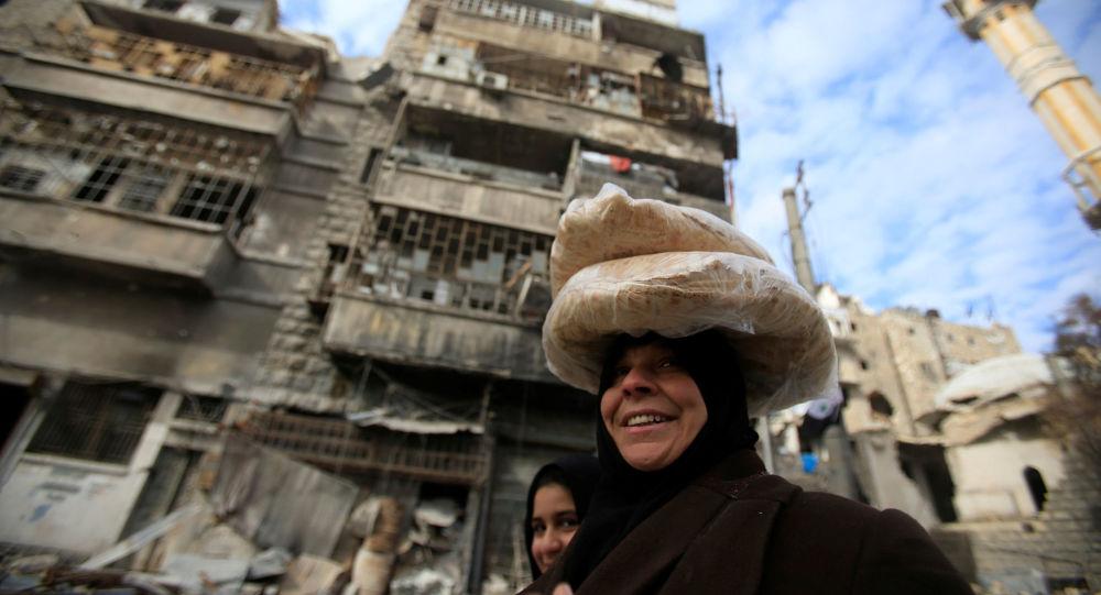 امرأة تحمل خبزاً في أحد شوارع حلب، 30 يناير/ كانون الثاني 2017
