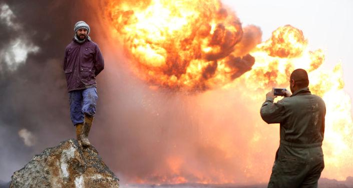 رجل يلتقط صورة لصديقه، بينما يقف الأخير على خلفية نيران مشتعلة ودخان كثيف، نتيجة اندلاع الحرائق في آبار نفط في القيارة، العراق، 30 يناير/ كانون الثاني 2017
