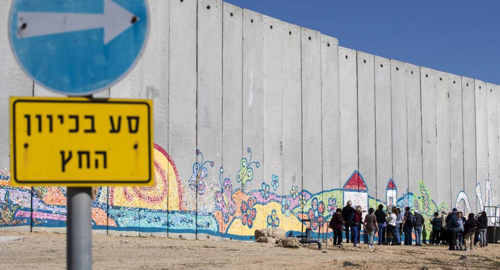 سياح إسرائيليون يلتقطون صوراً على خلفية الجدار الفاصل (عليه رسم الغرافيتي) على الحدود بين إسرائيل وقطاع غزة، 7 فبراير/ شباط 2017