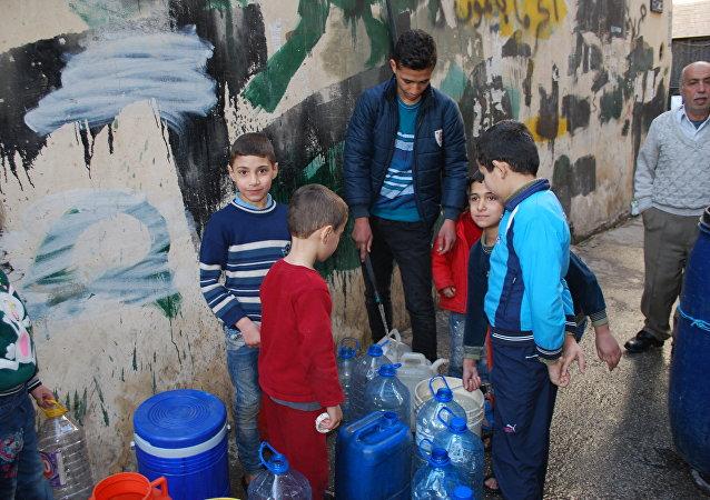 أطفال ينتظرون المياه في حلب