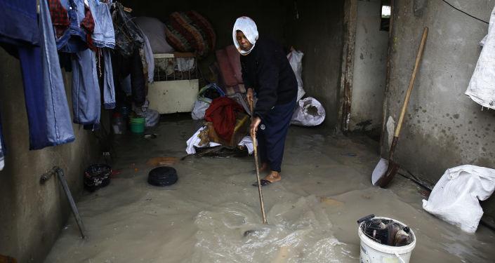 امرأة فلسطينية تقوم بتنظيف البيت من آثار فياضانات نتيجة أمطار غزيرة انهالت على مخيم جباليا، قطاع غزة، فلسطين 16 فبراير/ شباط 2017