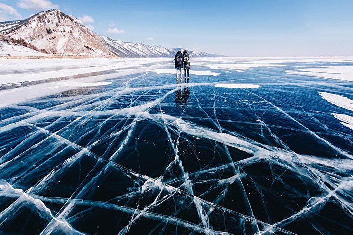 شخصان يلتقطان صورة فوق سطح بحيرة بايكال المتجمدة