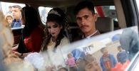 المتزوجان حديثاً، حسين زينو زعنون (26 عاما) وشهد (16 عاما) يجلسان داخل سيارة الفرح في مخيم خازر للنازحين، العراق، 16 فبراير/ شباط 2017