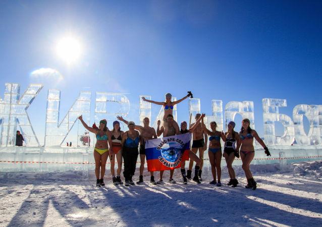 المشاركون في مهرجان للألعاب الشتوية زيمنيادا-2017 يلتقطون صورة جماعية على خلفية جملة محفورة من الثلج عِش في بايكال في إقليم إركوتسك.