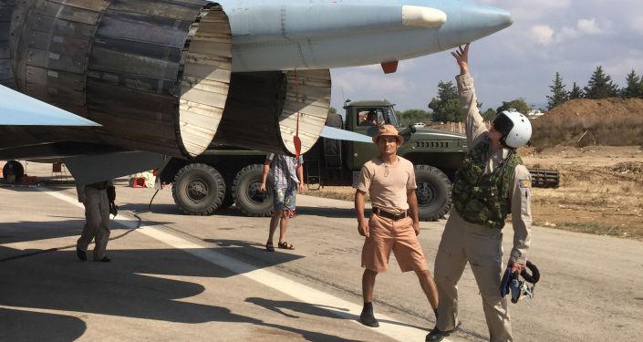 مجموعة من الطيارين الروس يسجهزون القاذفة سو-30 قبيل الإقلاع من قاعدة المطار العسكري السوري حميميم بسوريا