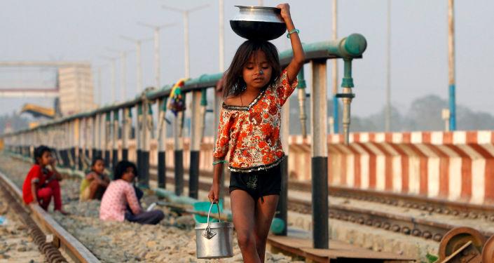طفلة تحمل وعاء بعد تعبئته بالماء وتسير على السكة الحديدية، الهند 28 فبراير/ شباط 2017