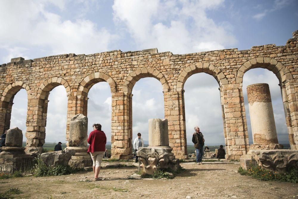 سياح متجمعون حول أقواس بازيليكا، وهي من أشهر الآثار الرومانية بالقرب من مكناس، المغرب 24 فبراير/ شباط 2017