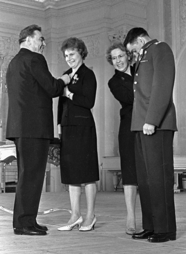 زعيم الاتحاد السوفيتي ليونيد بريجنيف (يسار) يكّرم كل من رواد الفضاء فالنتينا تيريشكوفا (وسط الصورة) وفاليري بيكوفسكي