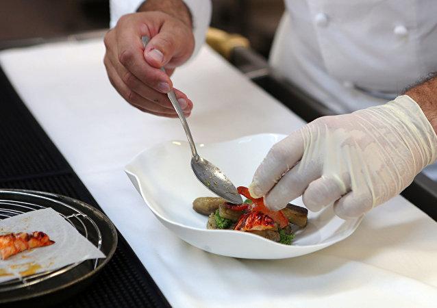 طباخ يحضر طبقاً في مطعم Idam بالدوحة.