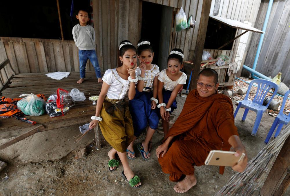 راهب بوذي يلتقط صورة سيلفي مع راقصات صغيرات قبيل بدء مراسم الاحتفال بيوم المرأة العالمي في بنوم بنه، كامبوديا 7 مارس/ آذار 2017