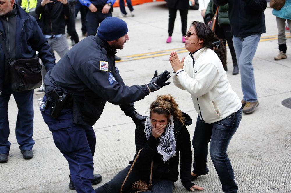 أحد أفراد الشرطة الأمريكية ينقذ أحد المتظاهرين، وذلك خلال مواجهات دارت بين المتظاهرين ضد لجنة الشؤون العامة الإسرائيلية الأمريكيةوالمؤيدين لها في مدينة واشنطن، الولايات المتحدة 26 مارس/ آذار 2017