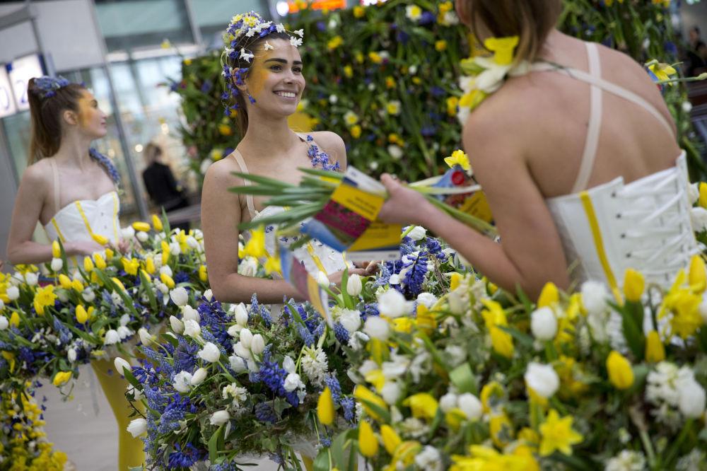 عارضات أزياؤ ترتدي أزياء مصنوعة من الأزهار الربيعية بمحطة القطار المركزية بمدينة أوترخت، هولندا 29 مارس/ آذار 2017