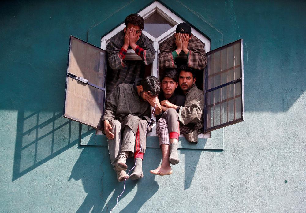 أشخاص يطلون من نافذة مسجد خلال جنازة أحد الأعضاء المسلحين (اسمه توصيف أحمد واغاي) والذي حسب وكالات الأنباء المحلية كان قد قتل نتيجة اشتباكات دارت مع عناصر قوات الجيش الهندية، تشادوره جنوب كشمير، الهند 29 مارس/ آذار 2017
