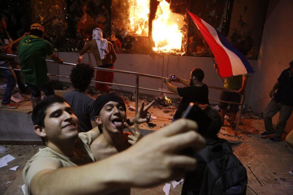 شابان يلتقطان صورة سيلفي على خلفية مبنى الكونغرس خلال المواجهات بين الشرطة المحلية والمحتجين في أسونسيون، باراغواي 31 مارس/ آذار 2017