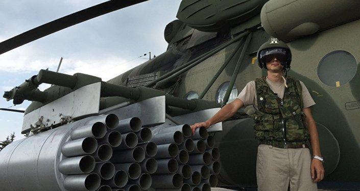 طيار يقف إلى جانب مروحية مي-8 أ.م.ش.ت في المطار العسكري السوري حميميم في سوريا