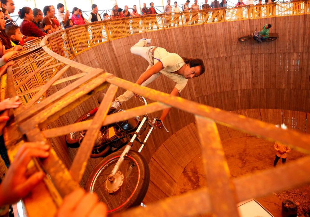 رجل يركب دراجة نارية داخل عجلة  ويل أوف ديث خلال مهرجان في بهاكتابور، نيبال 12 أبريل/ نيسان 2017