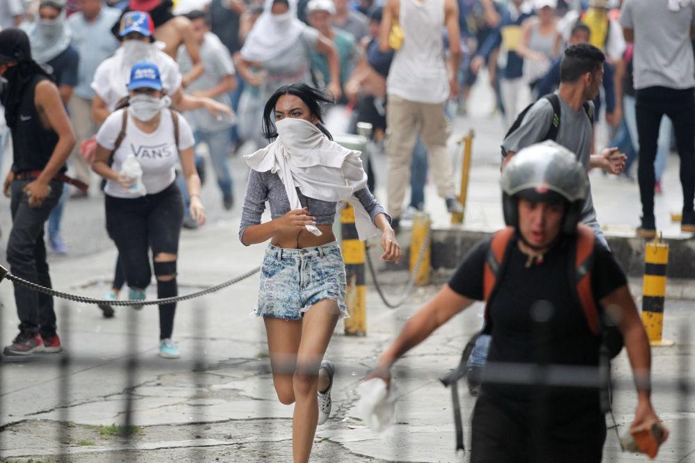 متظاهرون (ضد حكومة الرئيس نيكولاس مادورو) يهربون من الشرطة المحلية في كاراكاس، فنزويلا 10 أبريل/ نيسان 2017