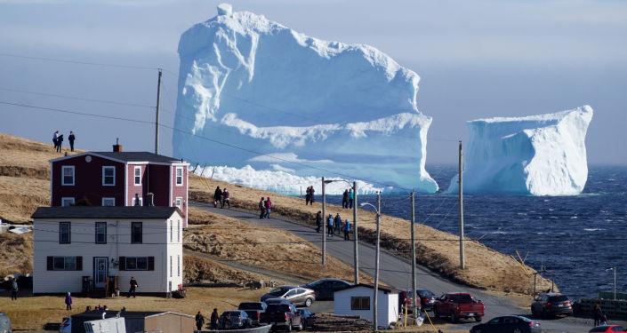 مواطنون كنديون يشاهدون عبور أول جبل جليدي يمر بمنطقة الساحل الجنوبي بالقرب من منطقة  فيريلاند نيوفاوندلاند، كندا 16 أبريل/ نيسان 2017