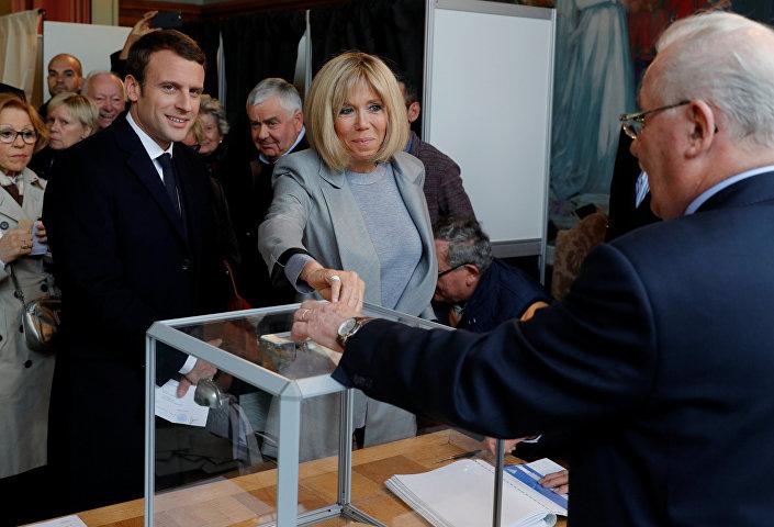 المرشح الرئاسي إيمانويل ماكرون وزوجته يدلون بأصواتهما في الجولة الأولى من الانتخابات الفرنسية