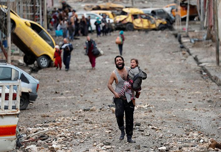 رجل حاملاً ابنته يجري من المناطق المسيطرة عليها من قبل تنظيم داعش الإرهابي في الموصل، العراق 4 مارس/ آذار 2017