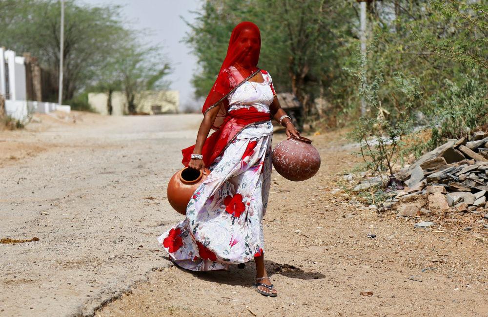 امرأة تحمل أوعية من الطين لتعبئتها بالماء في رجاستان، الهند 25 أبريل/ نيسان 2017