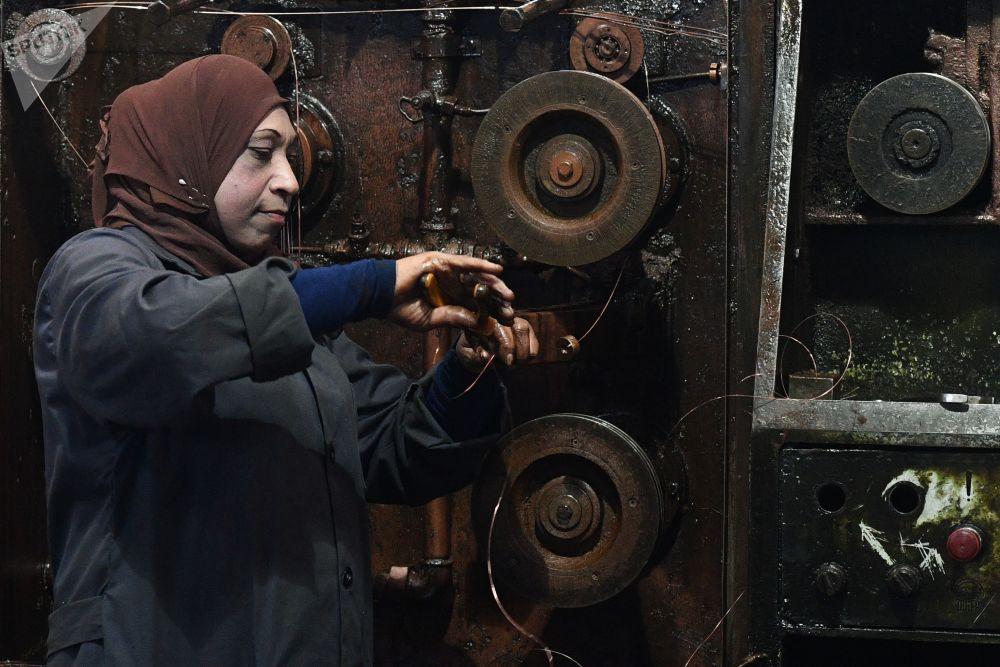 موظفة في مصنع حكومي لإنتاج الأسلاك الكهربائية في ريف دمشق، سوريا