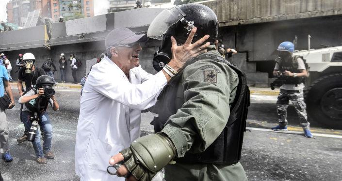 أحد المعارضين يجادل شرطي منالحرس الأمن القومي خلال الاحتجاجت في العاصمة كاراكاس، فنزويلا 22 مايو/ آيار 2017